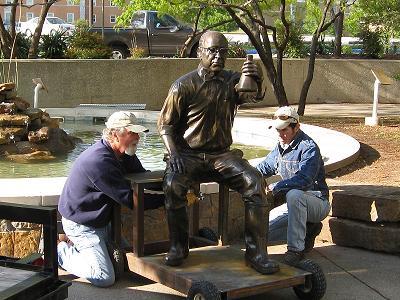 "Artist David Iles and assistant Vincent Villarfanca install bronze sculpture of ""Doc Silvey"""