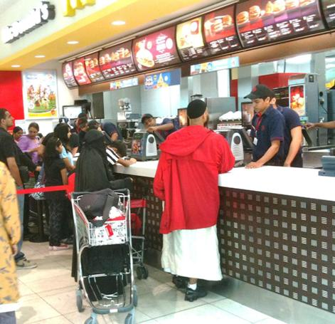 A women in a full burka at McDonalds at the Dubai Airport. Here, they are not hamburgers, they are beefburgers. Also, in Lahore, McDonalds delivers!