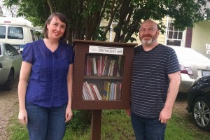 Amy Walton and James Garrett next to their Little Free Library, which they keep stocked with science books, classics and their favorite childrens' books-- in Spanish and English.