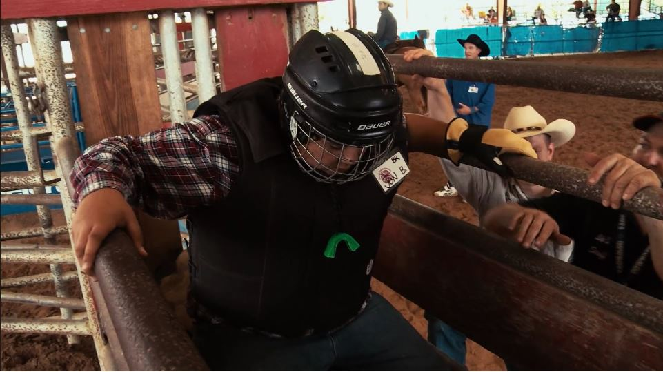 Jonathan prepares to ride a live bull at rodeo school.