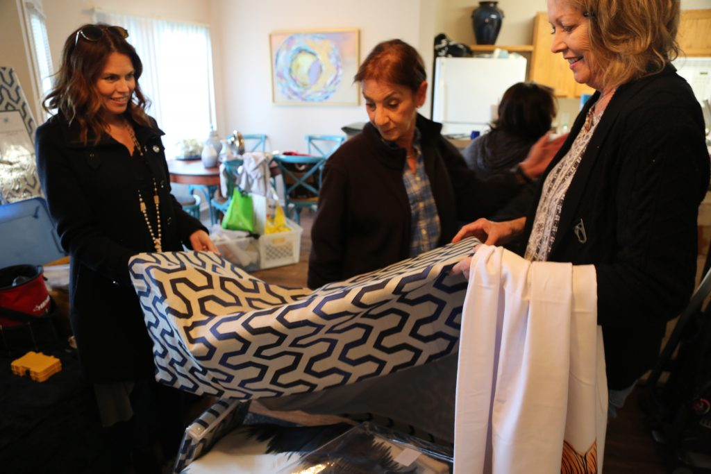 Dwell With Dignity Founder and Vice President Kim Turner admire drapes with volunteer. Photo: Hady Mawajdeh