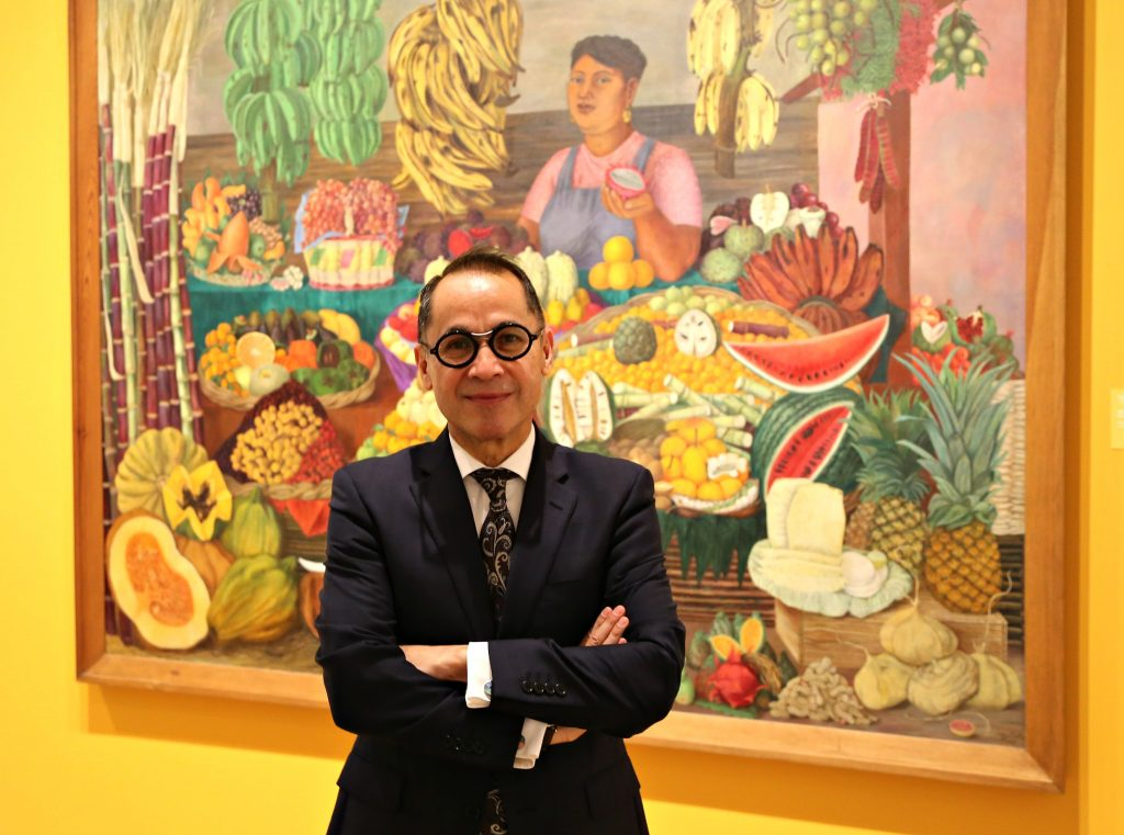 """The New DMA Director Agustin Arteaga posing in front of Olga Costa's """"The Fruit Seller."""" Photo: Hady Mawajdeh"""
