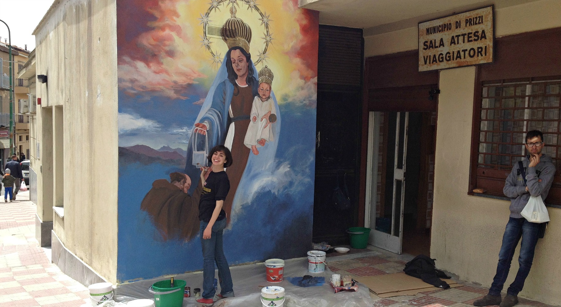 """Olivia Cole and her mural of Our Lady of Mount Carmel at the bus stop. The sign says: 'Municipal of Prizzi. Travelers Waiting Room."""""""