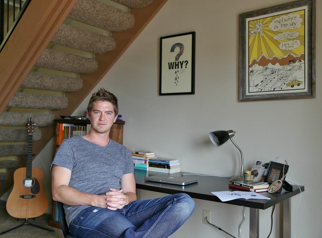 Poet Matt Morton sitting at his desk in his Denton apartment. Photo: Hady Mawajdeh