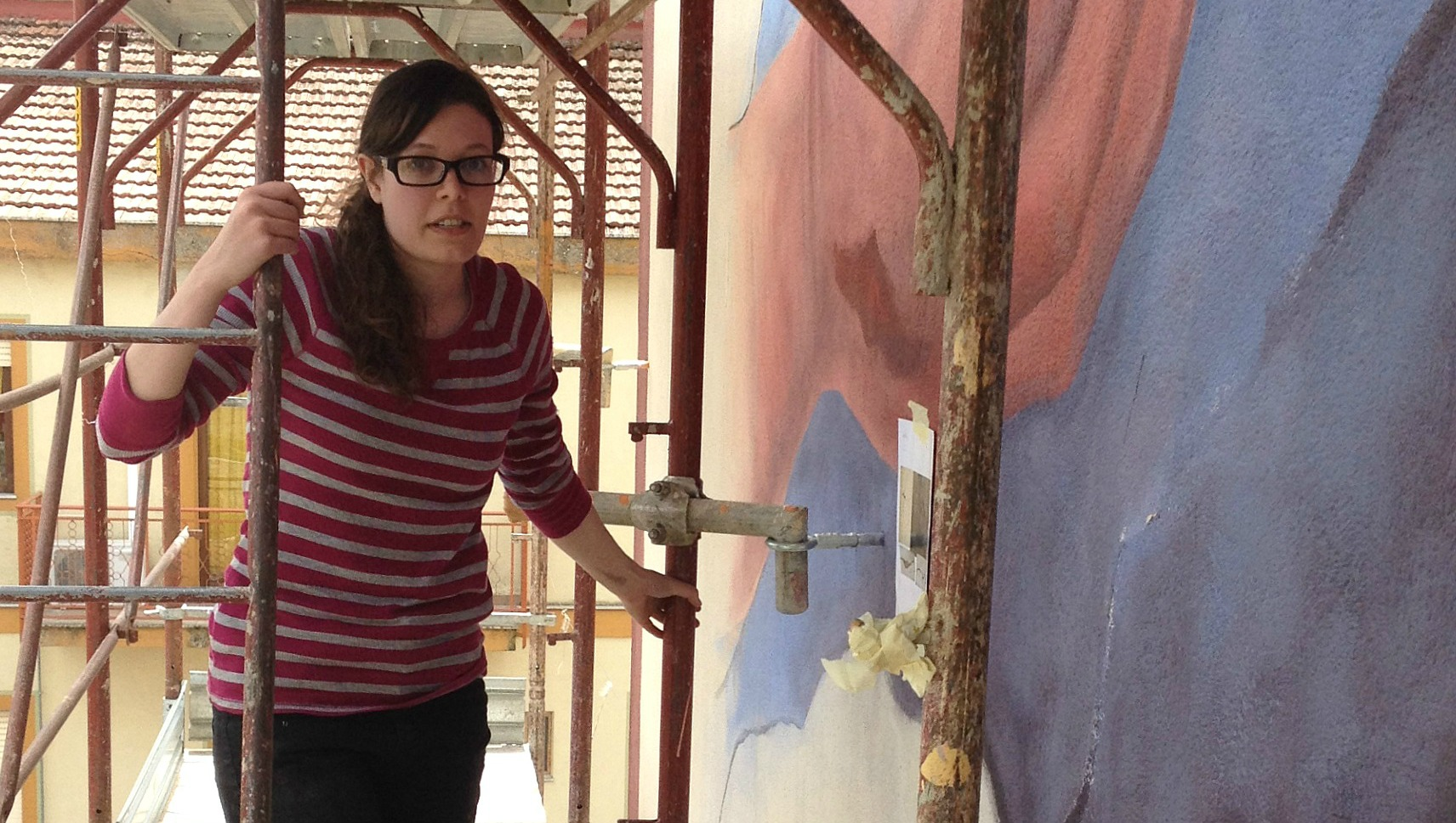 Maria Haag on the scaffolding for her mural of 'The Dance of the Devils' (Il Ballo dei Diavoli).