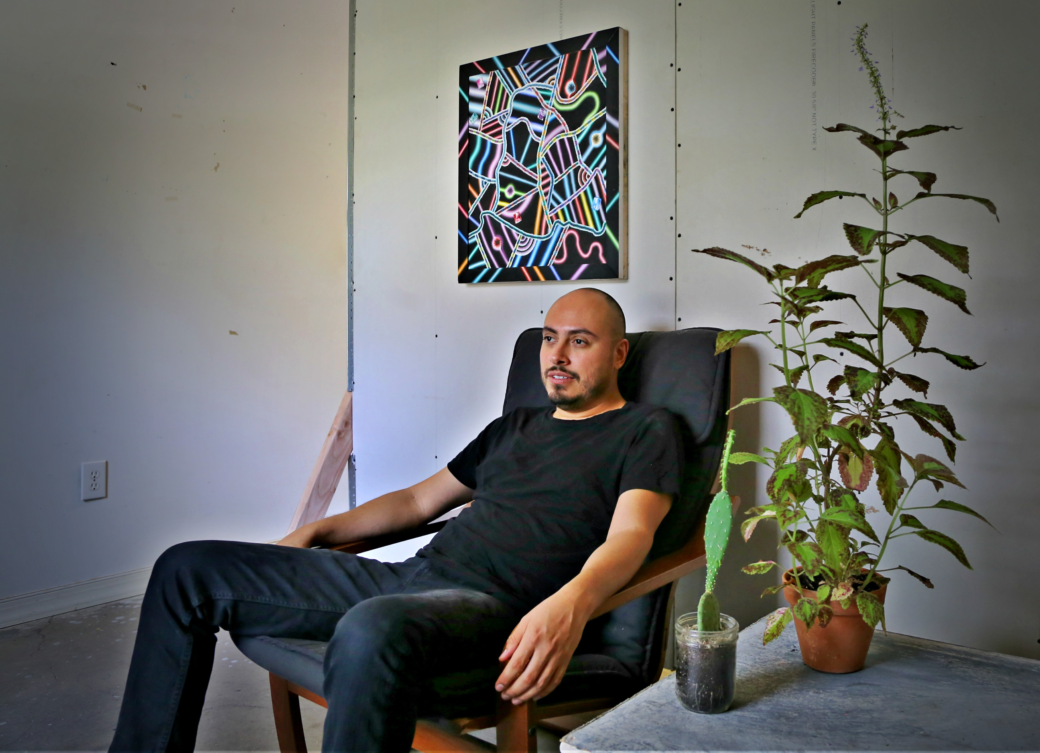 Arthur Peña sits in his studio. He says having plants in the room give him light and life. Photo: Hady Mawajdeh