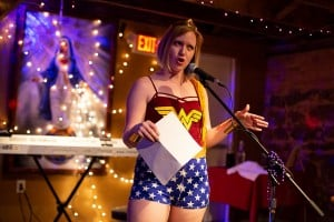 Donned in a Wonder Woman costume, Bonnie Jo Stufflebeam reads to the crowd. Photo: Leah Jones