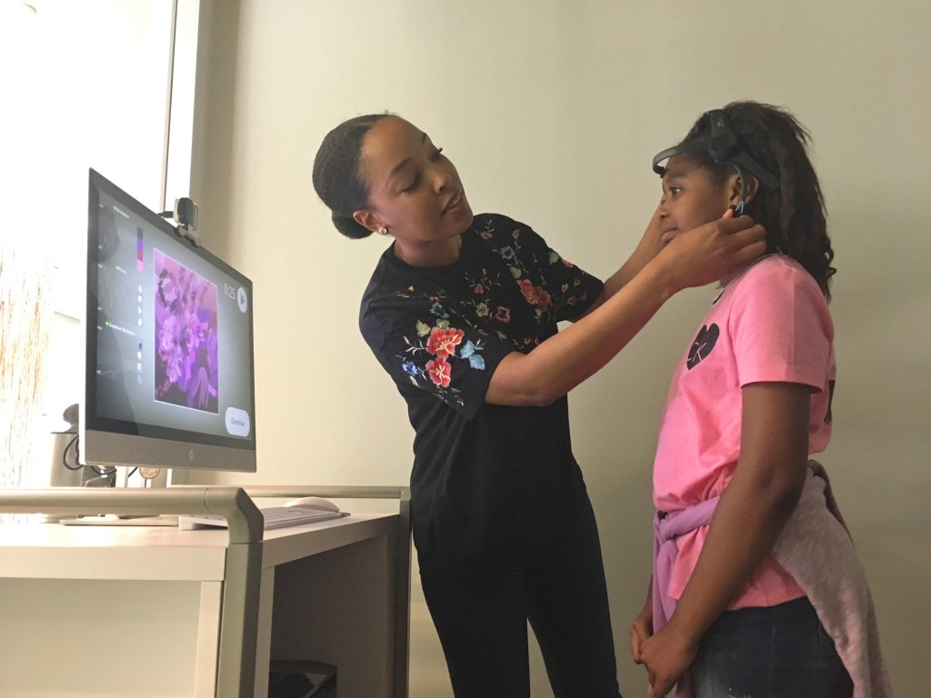 Courtney Johnson, an employee at Capital One, in Plano, Texas, helps a student adjust her EEG headset to create art using her brainwaves. Photo: Stella M. Chavez / KERA NEWS