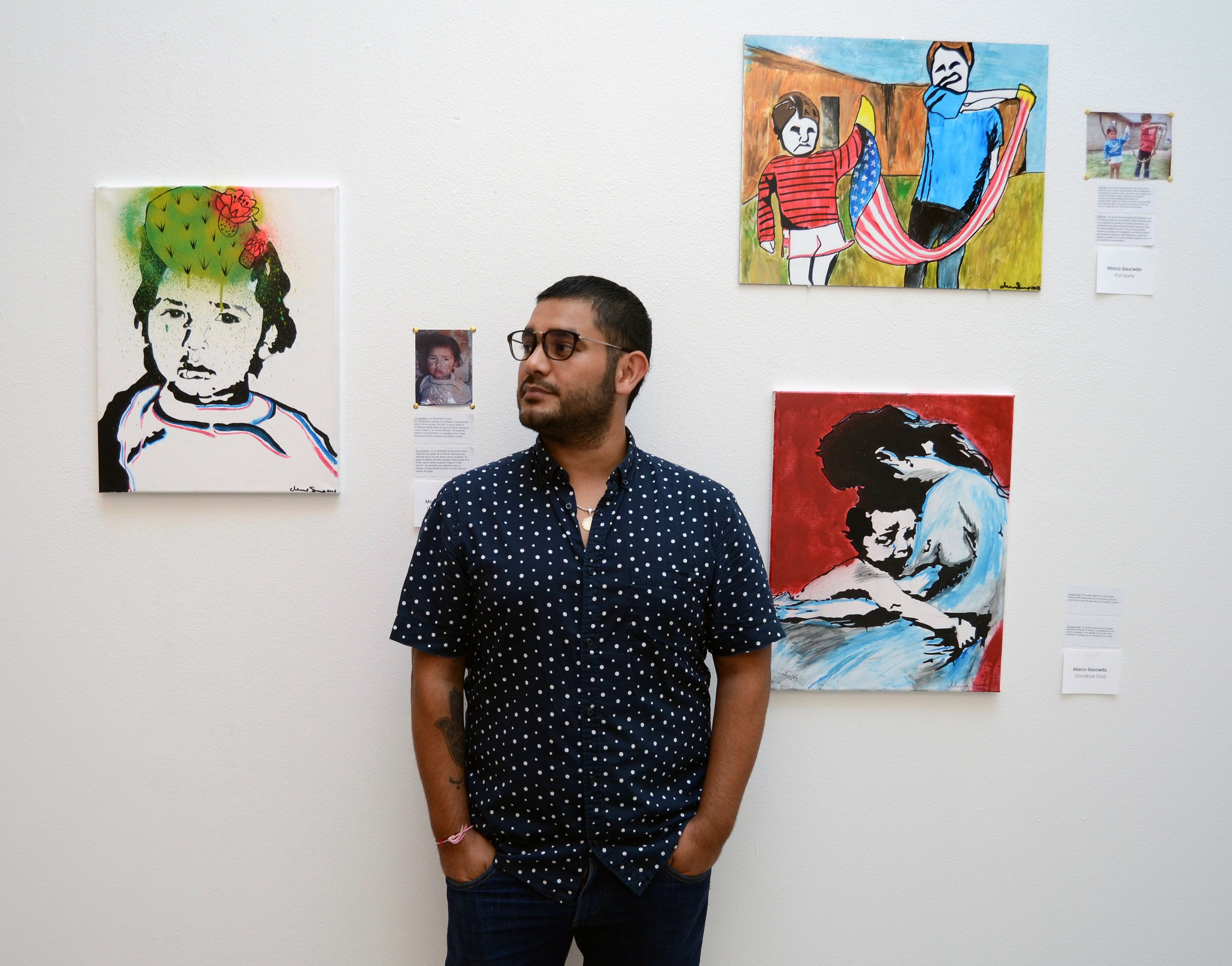 "Marco Saucedo with three of his paintings: ""De Nacimiento"" (left), ""Pal Norte"" (upper right) and ""Goodbye Dad"" (lower right). Photo: Olivia Peregrino"