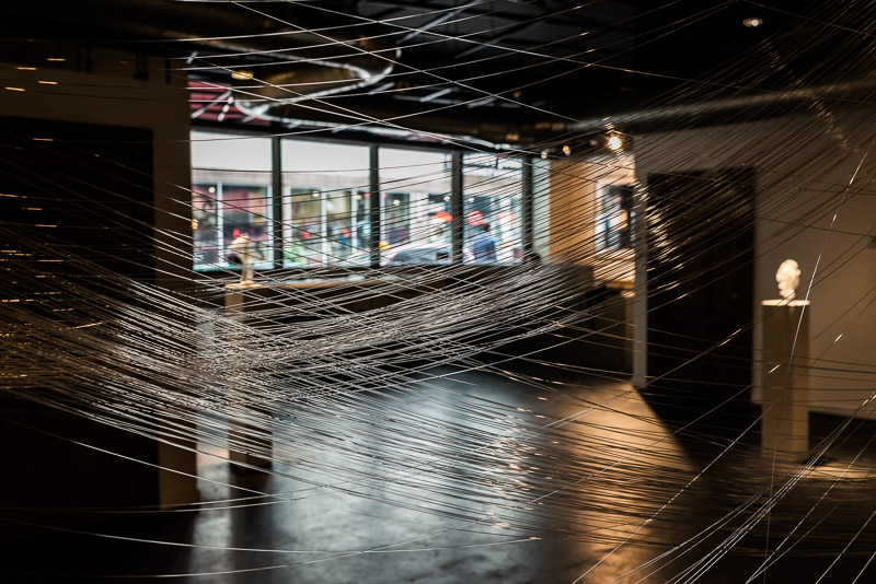 A view of the exhibition through the hand-pulled glass threads that comprise Justin Ginsberg's Existence No. 5: One Single Life.