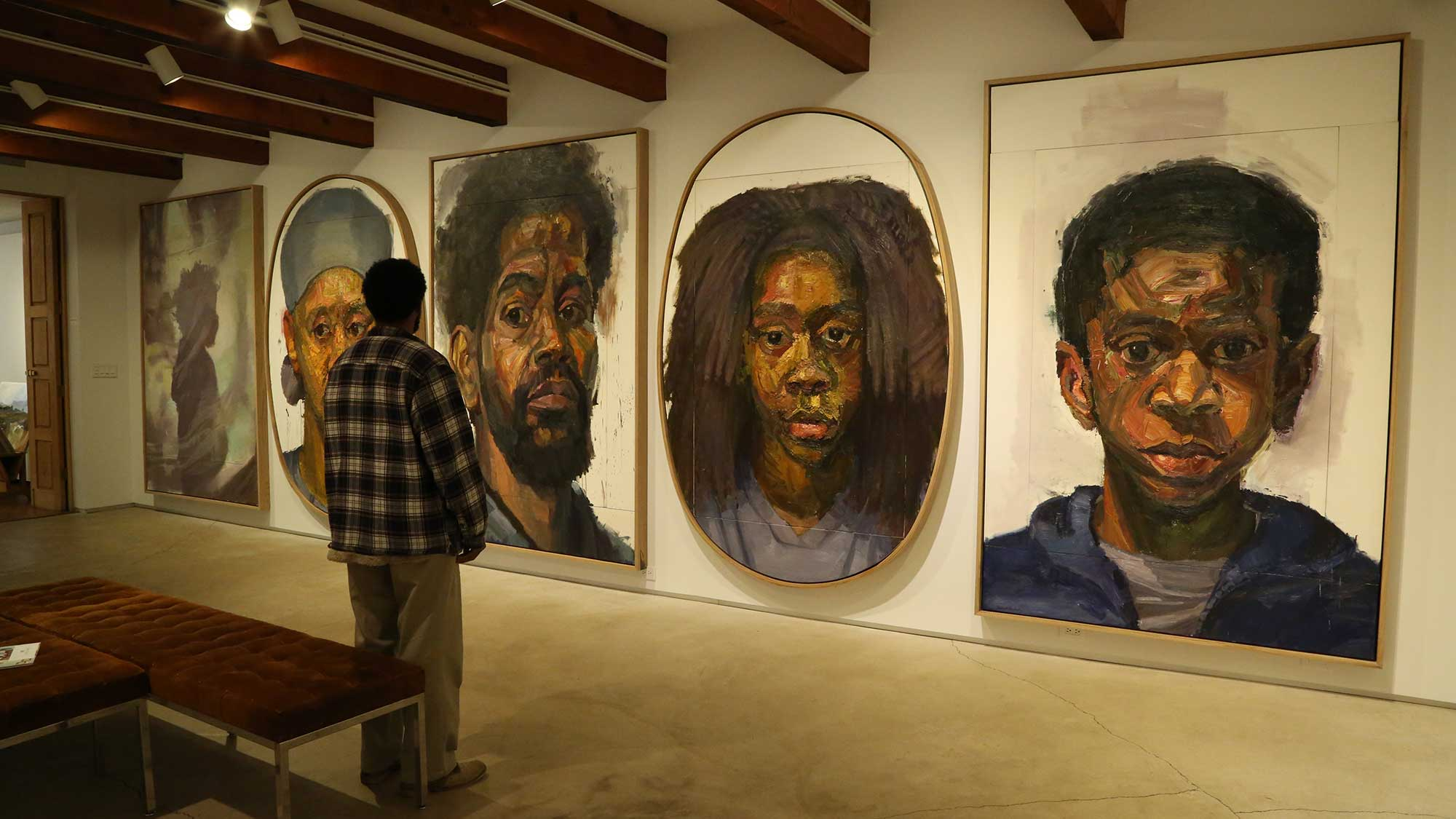Huckaby stands in front of a wall of his paintings.