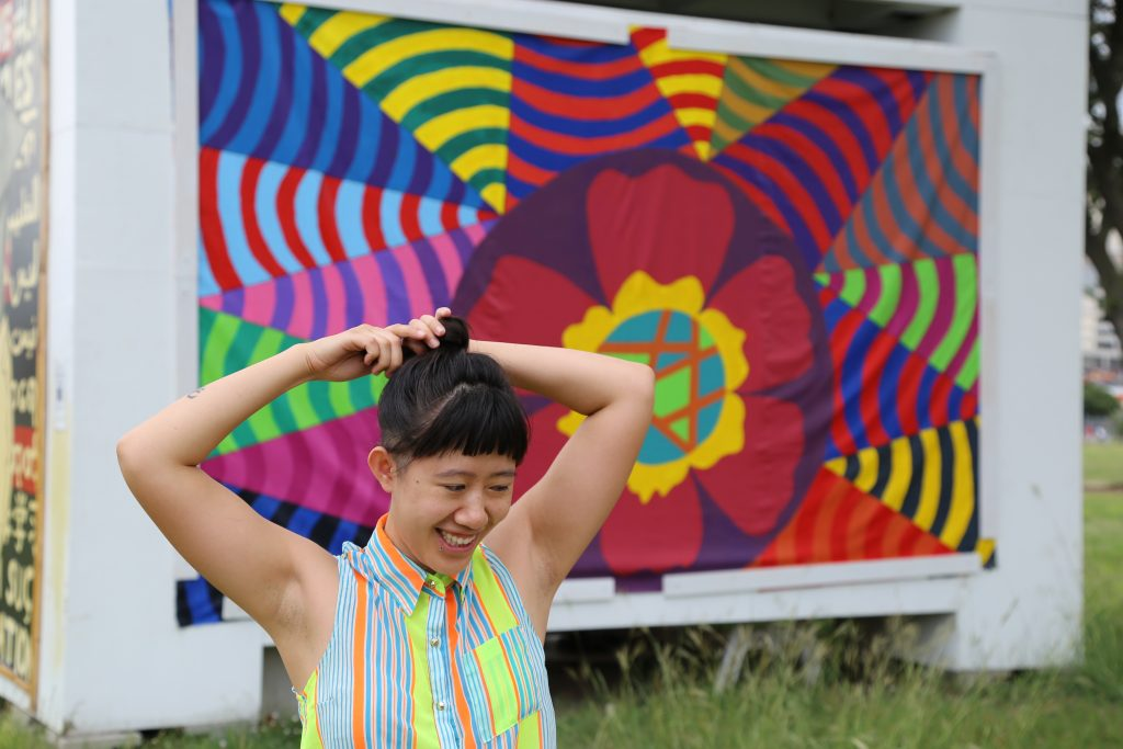 Zou stands in front of the first of three murals going up in Vickery Meadows that have been created by artists working at trans.lation.