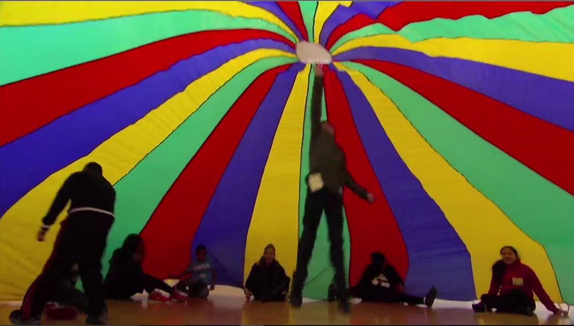 A child jumps to touch the top of the parachute in the Saturday day camp program at The Stewpot
