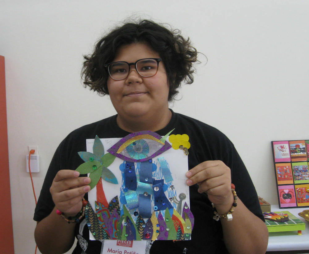 "Maria Patino holds an early collage depicting the eye. ""Instead of it crying sadness, it's crying beautiful, colorful tears and there there are plants growing up and spreading."" Photo: BILL ZEEBLE / KERA NEWS"
