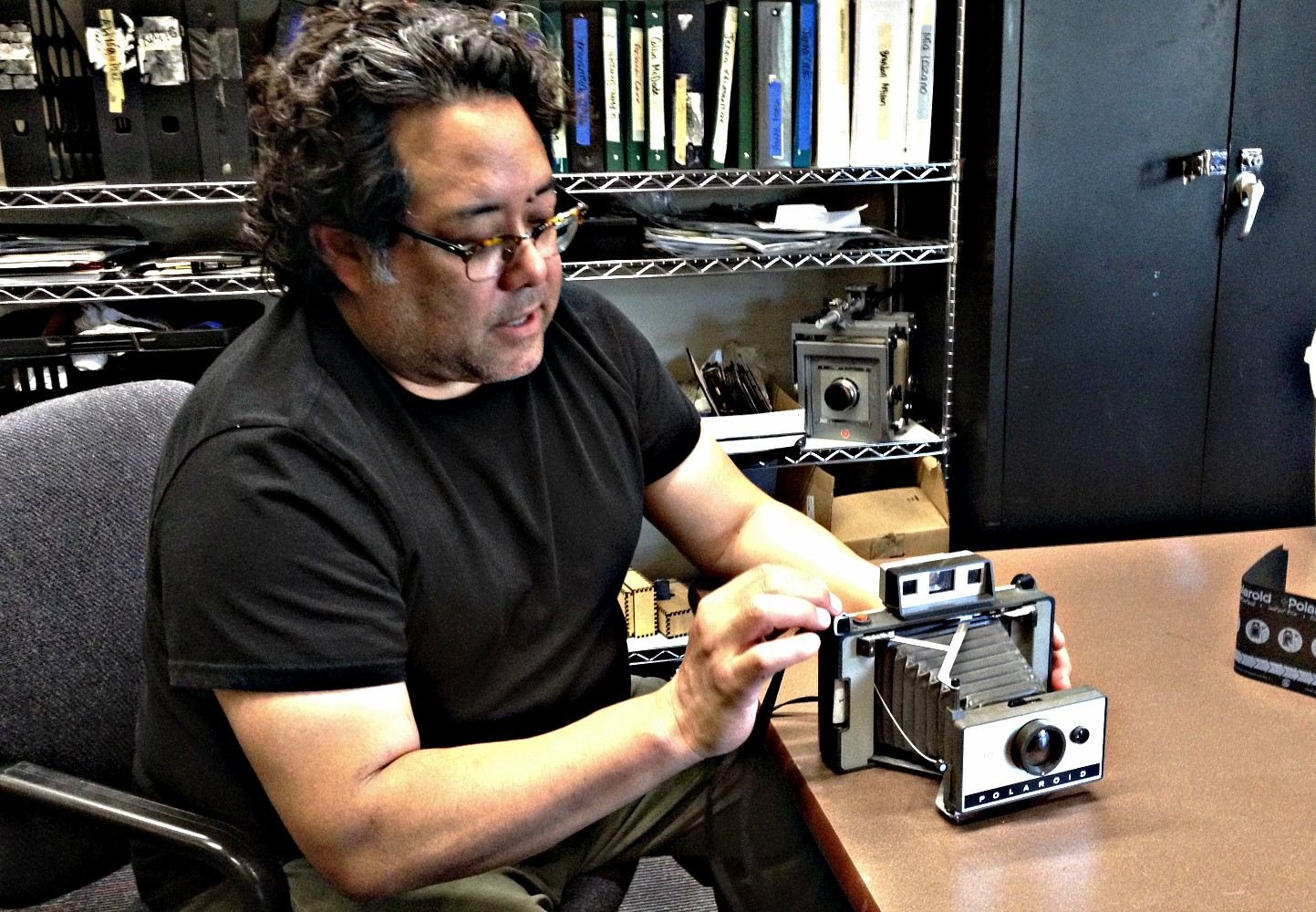 Frank Lopez in the Greenhill School photo lab with one of his Polaroids. Photo; Jerome Weeks