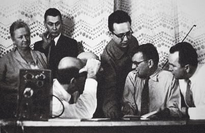 Anshel Brusilow, holding the violin bow, talks with Eugene Ormandy (left, with arm in front of face) and Dmitri Shostakovich (right) at a recording session in the early 1960s. Photo: Via UNT, but courtesy of Anshel Brusilow.