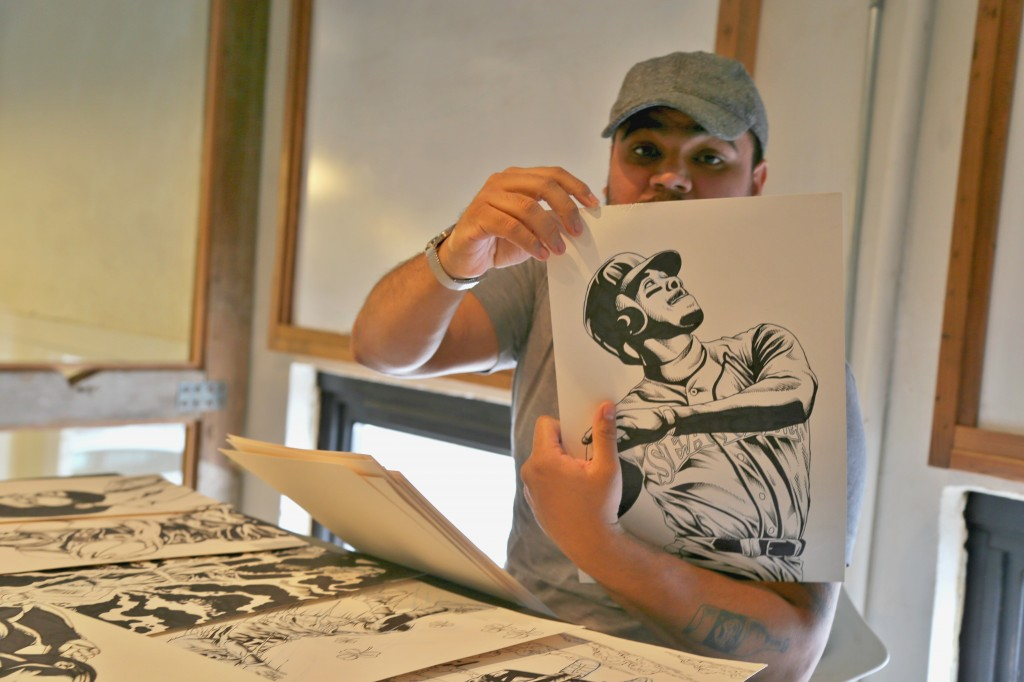 Illustrator Arturo Torres showing off some of his original drawings. Photo: Hady Mawajdeh