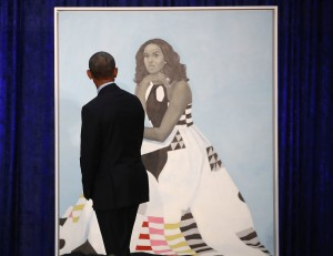 """Barack Obama gazes at his wife's newly unveiled portrait on Monday. The painting of Michelle Obama will be on display through November in the National Portrait Gallery's """"Recent Acquisitions"""" section. Photo: Mark Wilson/Getty Images via NPR"""