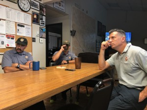 Fort Worth Firefighters listen attentively at Fire Station 31 as artist Joe Barrington describes his artwork. Photo: Hady Mawajdeh