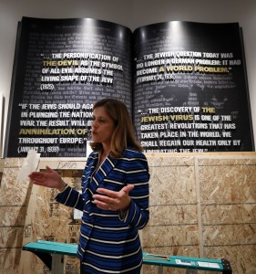 Higgins standing in front of the book-like sculpture featuring quotes from Hitler. Photo: Courtesy AP Photo/Tony Gutierrez