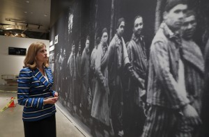 In this July 29, 2019, photo, Dallas Holocaust and Human Rights Museum President and CEO, Mary Pat Higgins, pauses as she gives a tour of the museum in Dallas, to look at a wall size image of Jews marching. When Dallas' Holocaust museum reopens in a few weeks it will not only be in a new building five times the size of its previous location, but will take visitors on a journey that also includes modern-day genocides and the evolution of human and civil rights in the U.S. Photo: AP Photo/Tony Gutierrez