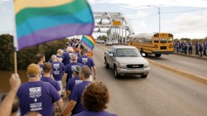 Group wearing purple t-shirts and carrying Pride flag cross Edmund Pettus Bridge.