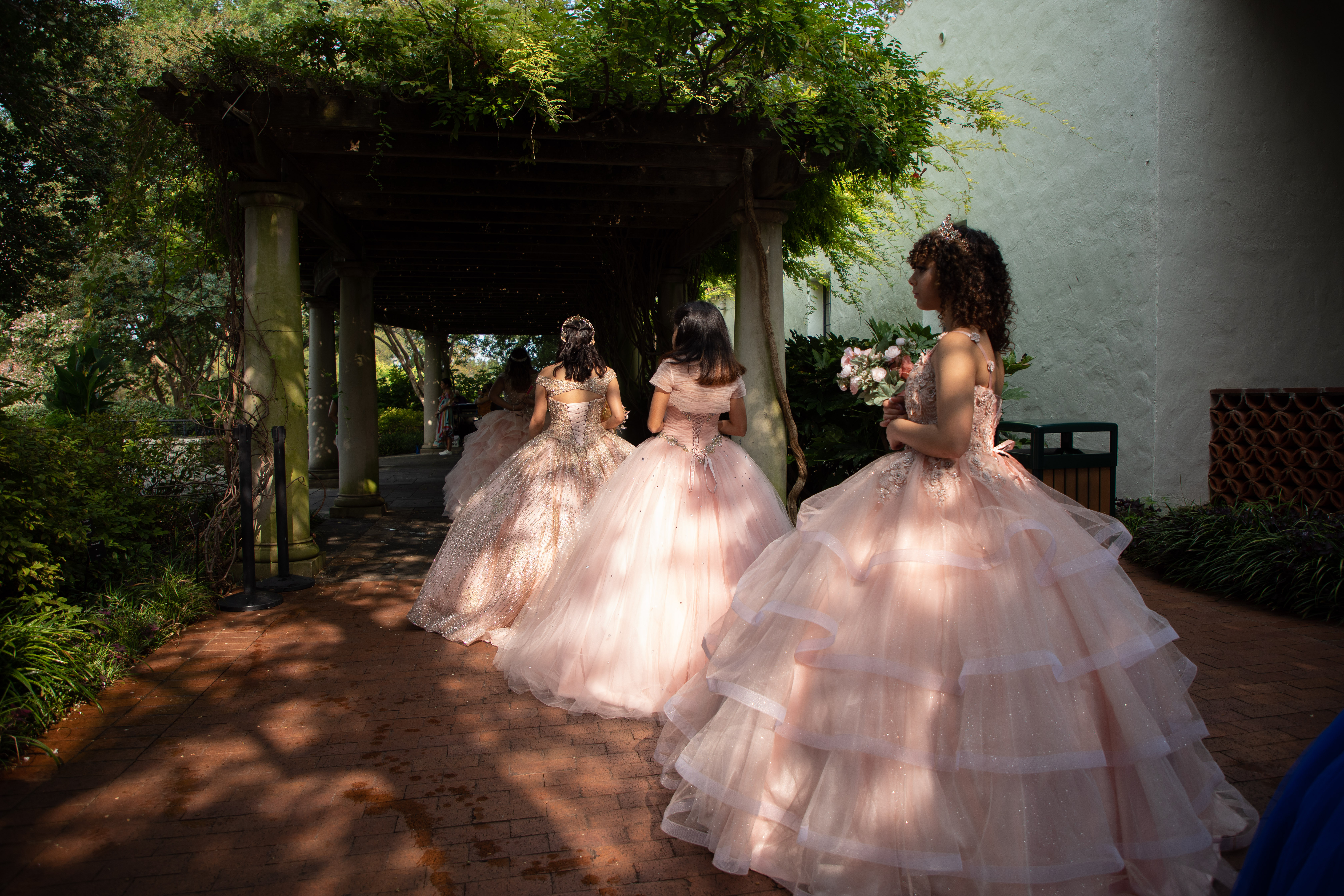 Photo of three girls in pink puffy Quince dresses on stage at the Dallas Arboretum.
