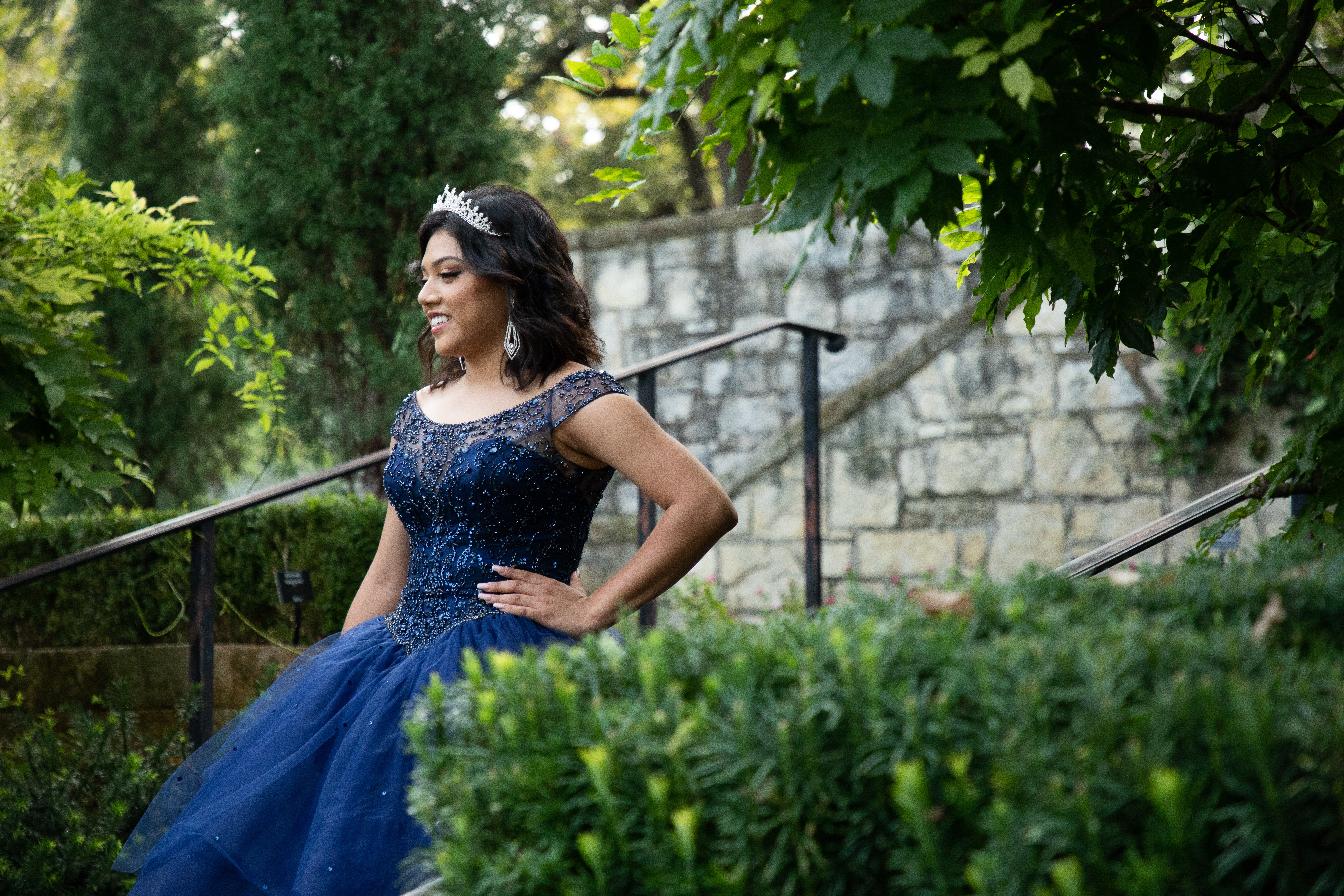 Photo of Yailyn Gomez in her blue dress with lots of sparkles and a crown on the stairs at the Dallas Arboretum.