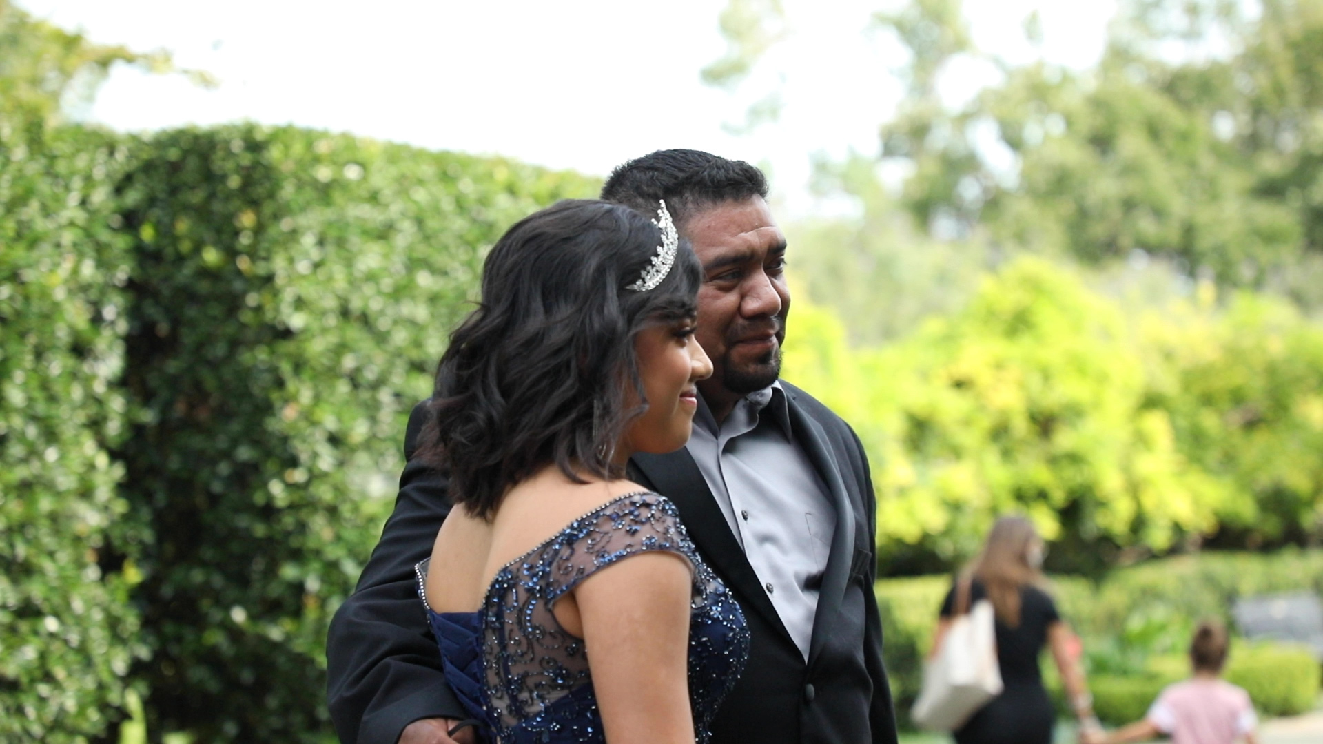 Yailin in her Quince dress posed with her father in a tux at the Dallas Arboretum.