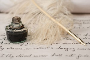 ink bottle and feather quill pen laying on parchment with writing