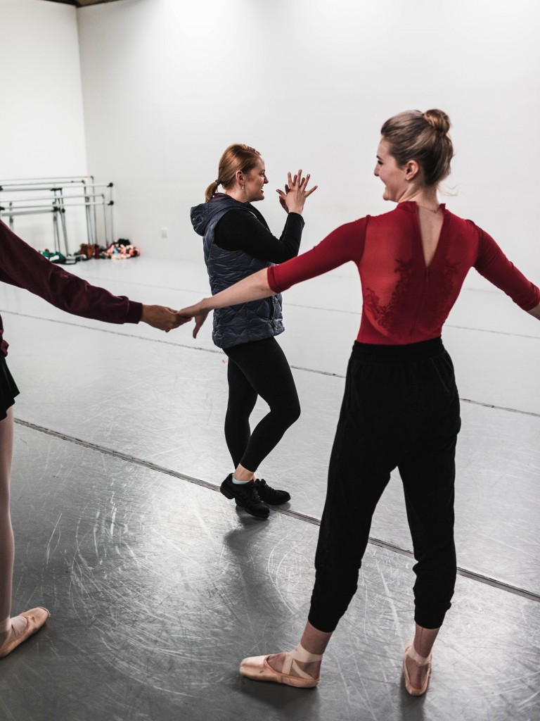 Three dancers talking and holding hands in a studio.