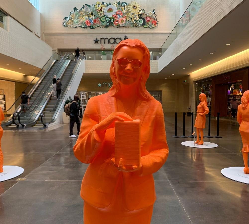 A orange life-size 3D printed figure of Minerva Cordero stands in NorthPark Center.