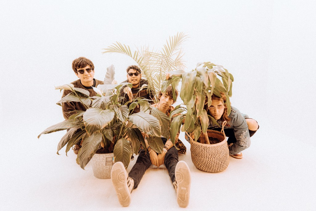 The four member band, Kyoto Lo-Fi, sits on the ground. Members are surrounded by plants.