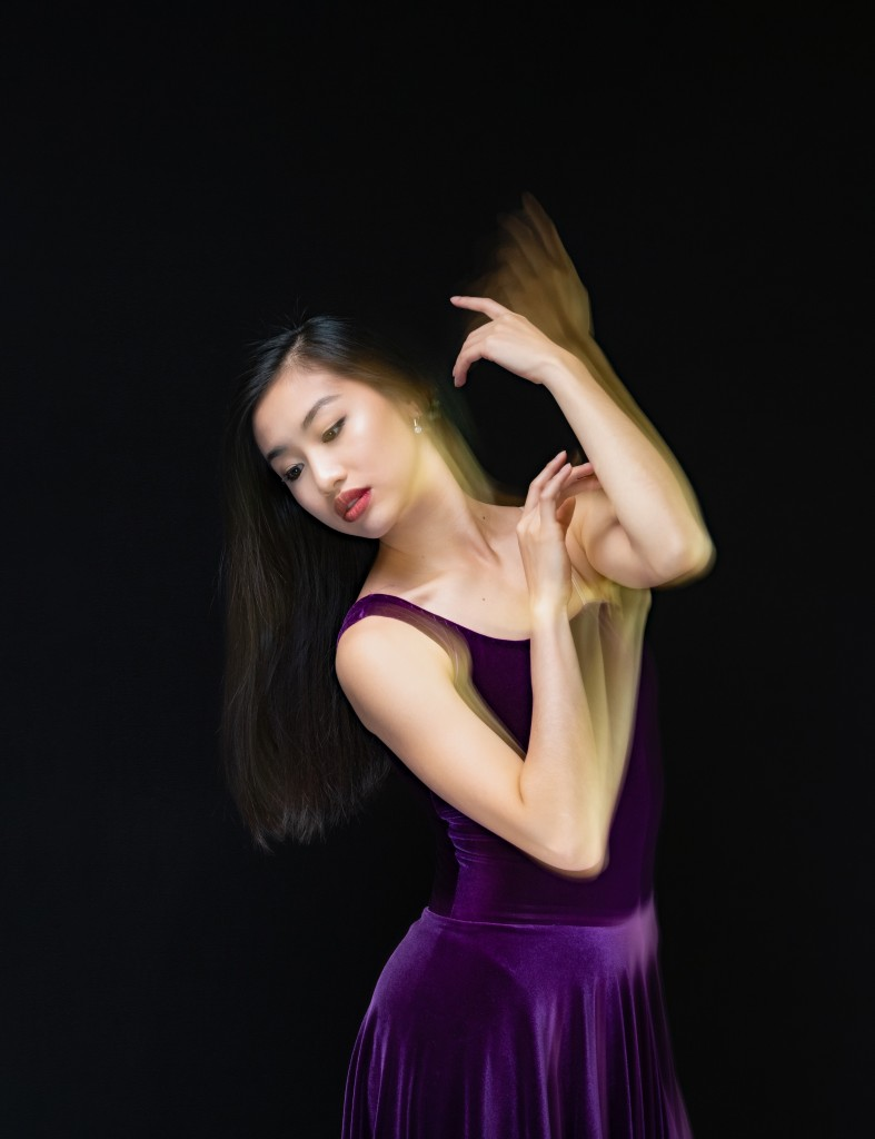 A young dancer in a purple dress holding up her arms.