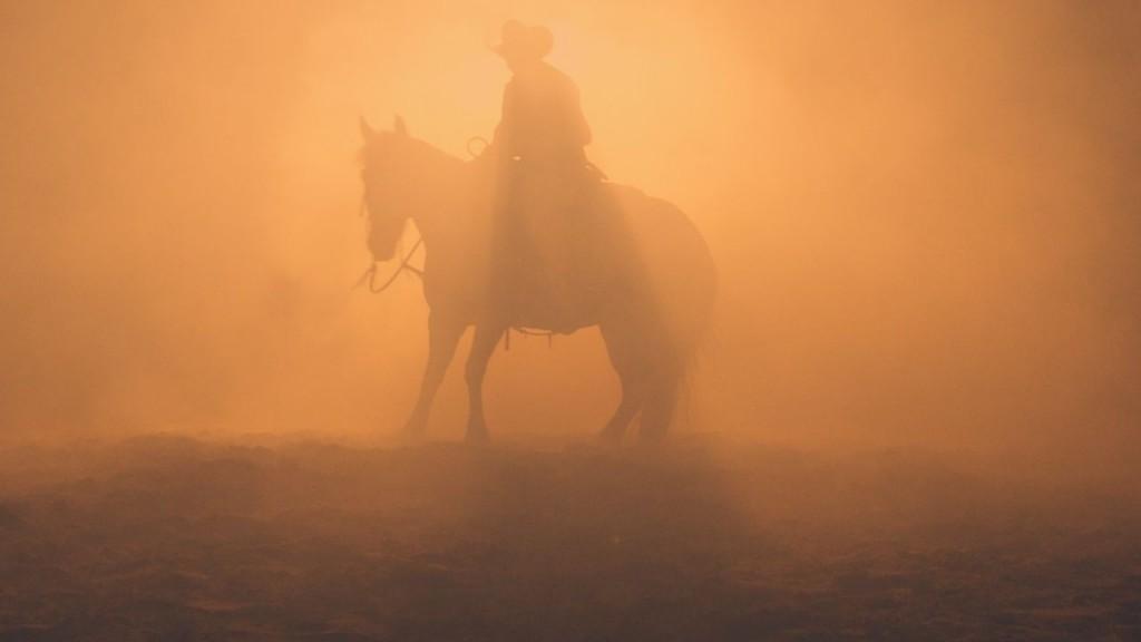 Ascension Bañuelos rides a horse in orange gloomy lighting.