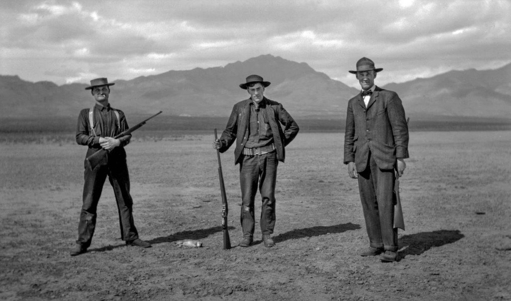 Three men, dressed in early 20th century attire, pose for a photo in front of western landscape.