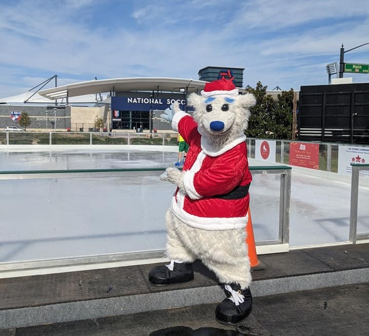 someone in a polar bear costume standing near the Frisco Square ice rink