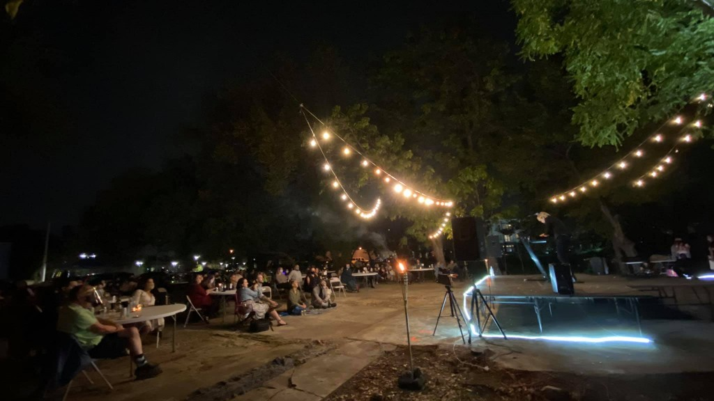 Wide shot of a performance at night at an outdoor venue.