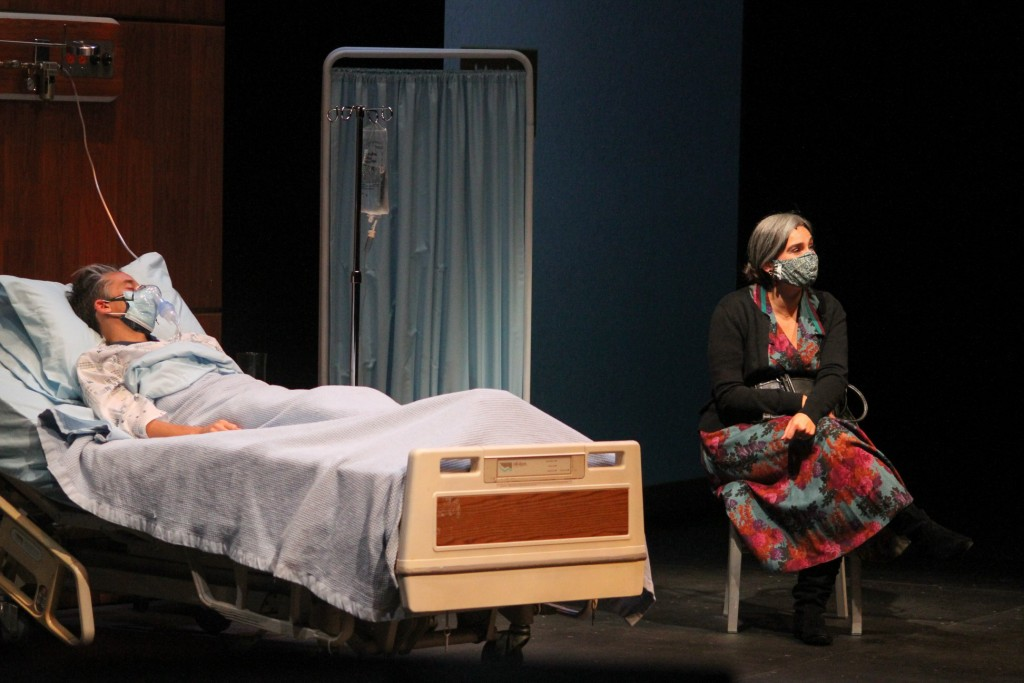 Scene from the play, 'In the Bleak Midwinter.' Man laying in hospital bed. Older woman sitting on stool next to bed.