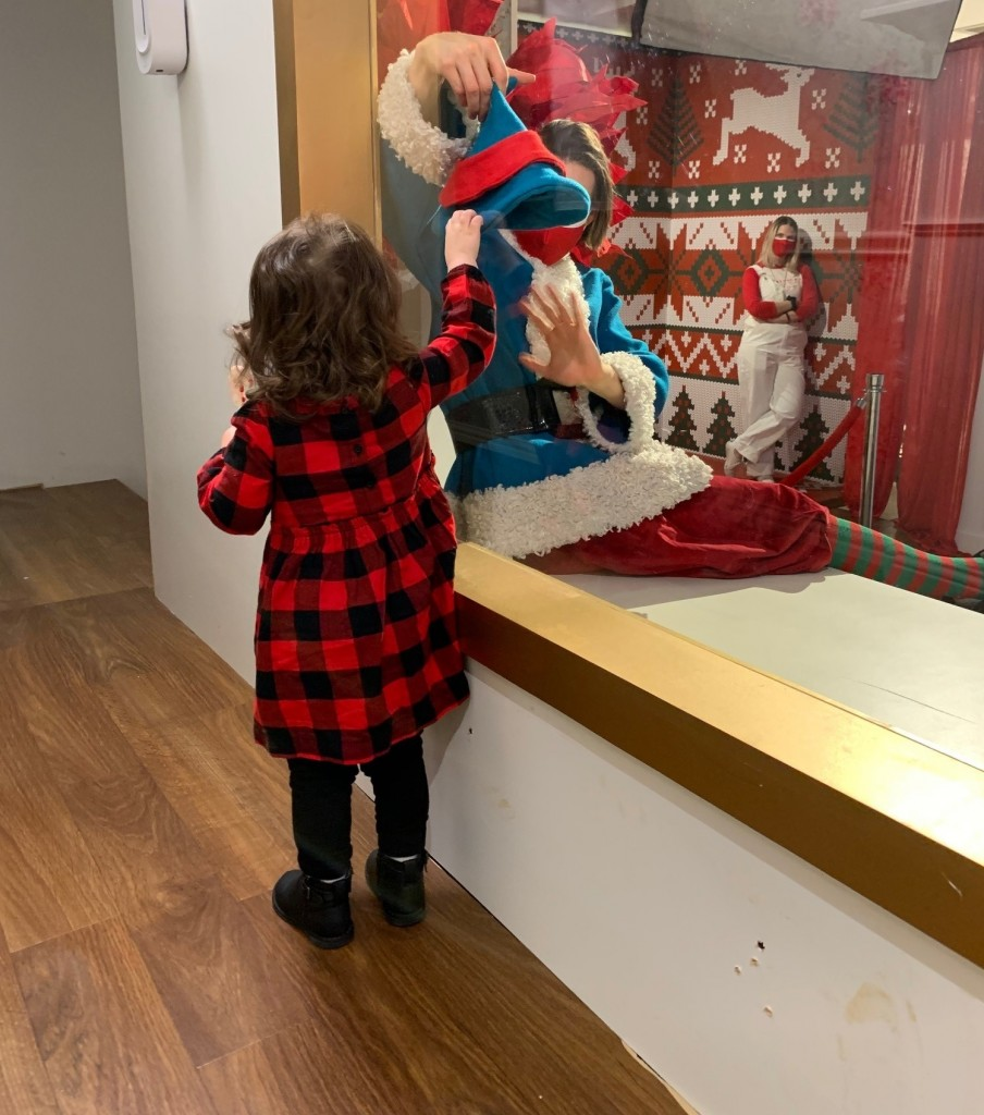 A toddler reaches out to an elf, behind a plexiglass window, at the Galleria Dallas' Snow Day exhibit.