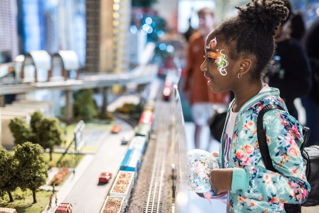 Young girl looking with delight at miniature trains.