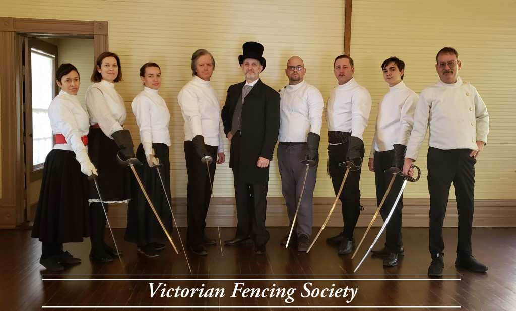 Group photo of Victorian Fencing Society at their Grand Assault of Arms Exhibition in 2019. The group is made up of two women and seven men. They are in Victorian dress and pointing swords on the ground.