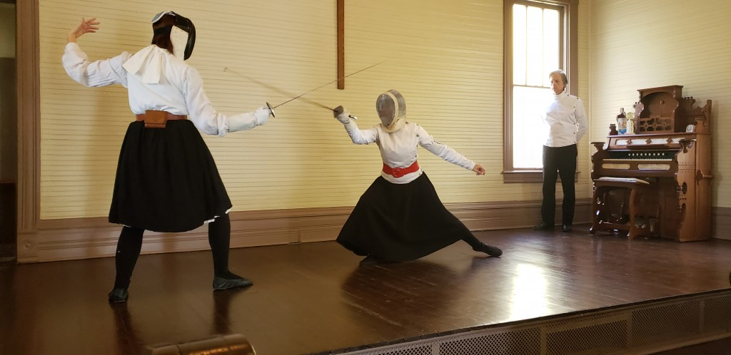 Two women fencing in period Victorian clothes.