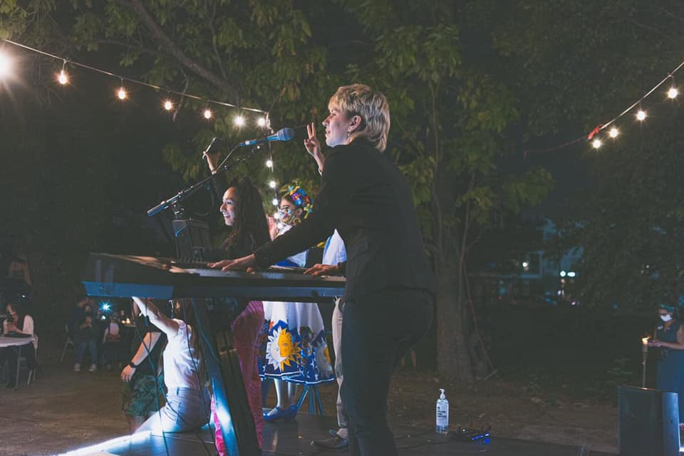 Musician Poppy Xander playing keyboard on stage at outdoor venue.