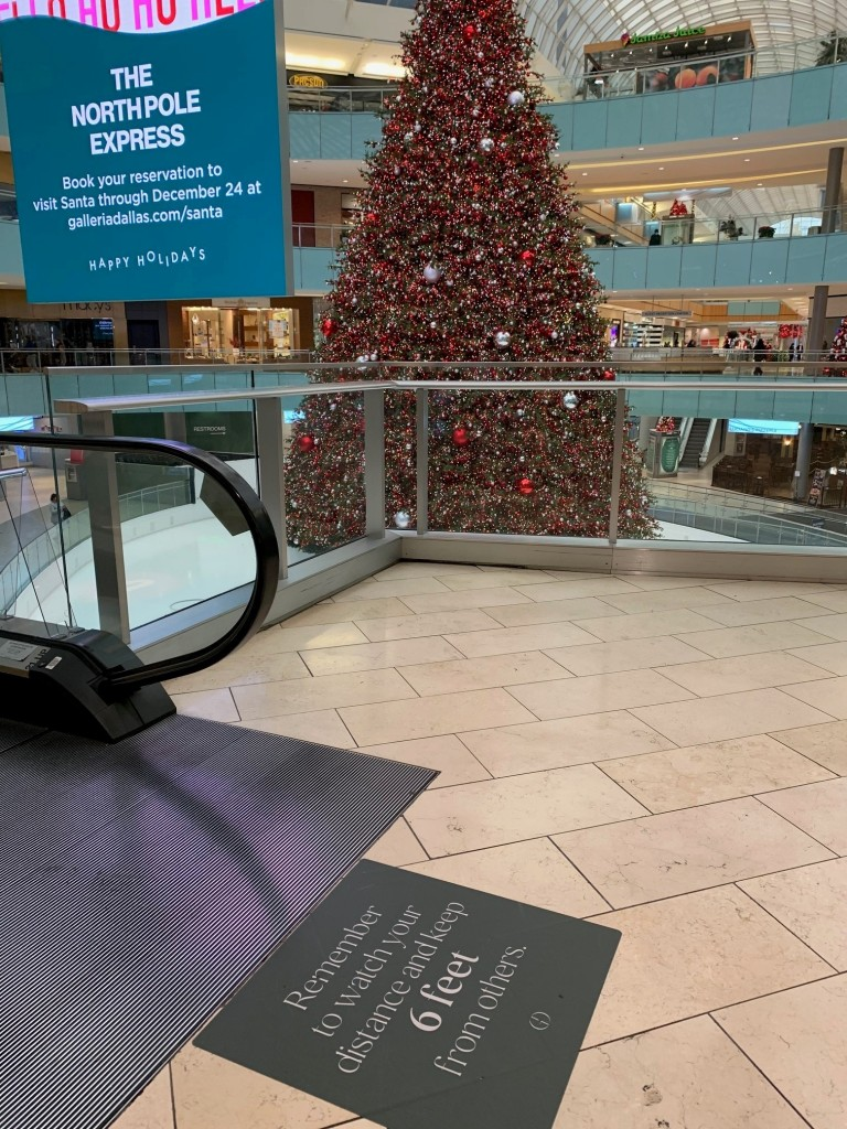 "The giant indoor Christmas tree at the Galleria Dallas and a floor sign that reads ""Remember to watch your distance and keep 6 feet from others."""