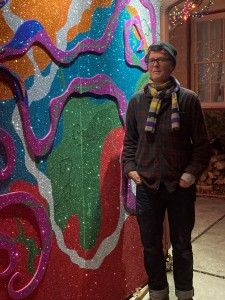 Liz Simmons, the creator of Electric Lizzyland, stands by a multicolored glitter wall.