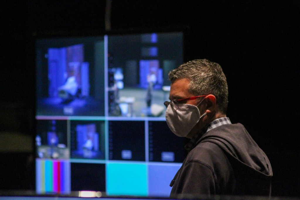 Artistic Director of DTC, Kevin Moriarty wears a mask and stands in front of TV monitors
