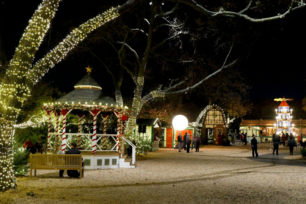 A nighttime view of Dallas Arboretum's Christmas Village. Holiday lights decorate European style buildings