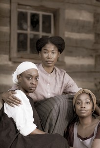 Three African American women seated on the steps of a log cabin. The women are dressed as slaves from the 1840s.