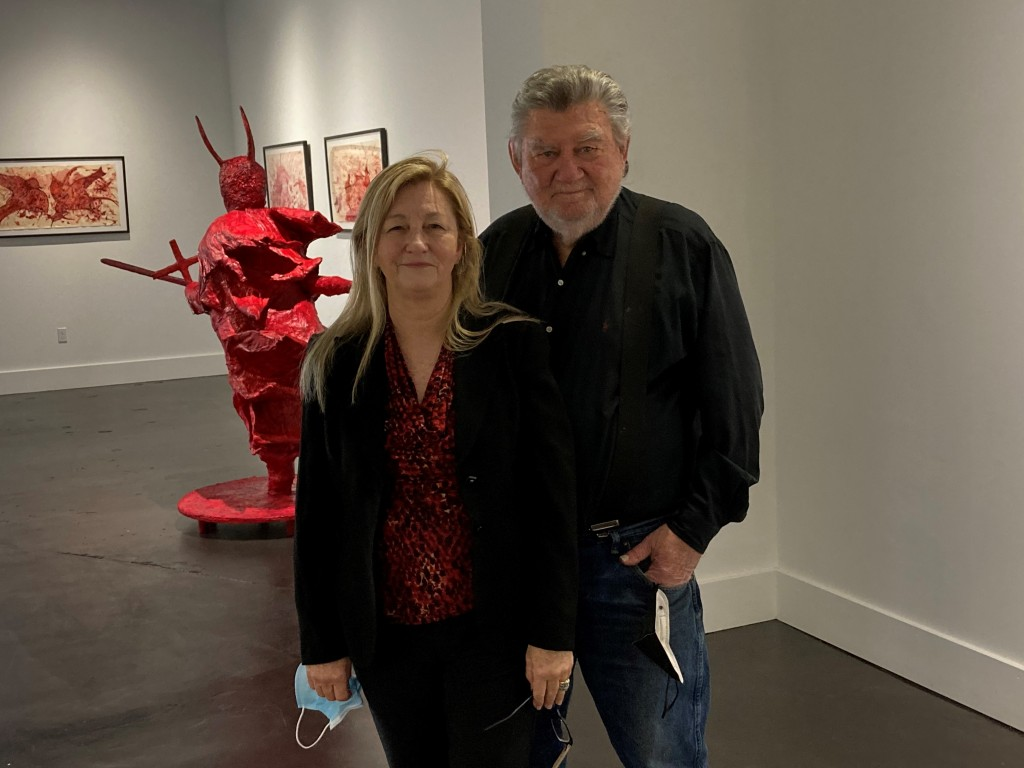 Artists Charmaine Locke and James Surles. Surles is large older man with gray hair and beard. He's wearing a dark shirt and jeans. Locke is middle aged with blonde hair wearing a black suit with a red and black blouse. Both are standing in gallery in front on their works.